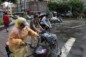 People wearing raincoasts and holding umbrellas commute as Typhoon Talim approaches, bringing sporadic wind and showers in Taipei, Taiwan, on Sept 13, 2017.