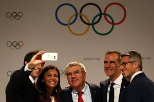 Paris and LA representatives pose for a selfie with IOC president Thomas Bach (centre) in Lima.