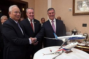 Mr Najib Razak shaking hands with Mr Kevin McAllister, chief executive officer of Boeing Commercial Airplanes, at a memorandum of understanding exchange ceremony between Boeing and Malaysia Airlines in Washington on Wednesday. With them is Malaysia A