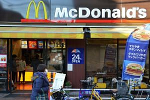 Passersby walk past a McDonald's store in Tokyo.