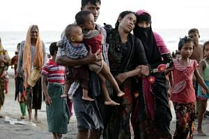 A sick Rohingya woman and her husband and children move towards a van after disembarking from a boat on Sept 14, 2017.