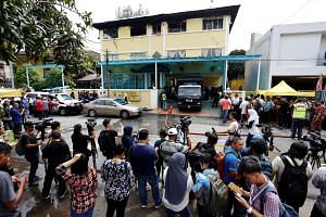 A crowd gathering outside the Darul Ittifaqiyah Tahfiz in Kuala Lumpur yesterday, where a fire killed 23 students and two teachers.