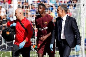 Barcelona's Ousmane Dembele receives medical attention after sustaining an injury.