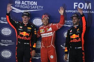 Top qualifier German Formula One driver Sebastian Vettel of Scuderia Ferrari (centre) gestures next to Australian driver Daniel Ricciardo (right) and Dutch Max Verstappen of Red Bull Racing Tag Heuer, after the qualifying round on Sept 16. 2017.