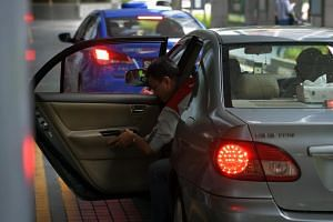 A passenger getting off a private-hire car at the taxi stand of International Plaza.