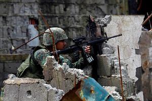 A government soldier from Philippine Marines 1st Brigade takes up a position as troops continue their assault on clearing operations against the pro-Islamic State militant group in Marawi city, southern Philippines, Sept 14, 2017.