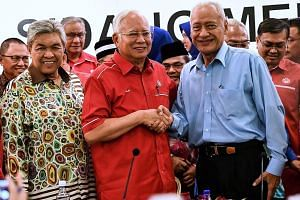 Malaysian Prime Minister Najib Razak, who is also Umno president, shaking hands with former Selangor menteri besar Muhammad Muhammad Taib as he welcomes the latter back to the ruling party.
