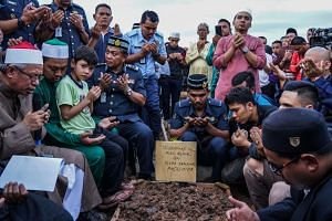 Malaysians offer prayers for a victim of the Darul Quran Ittifaqiyah Tahfiz Centre fire during a burial ceremony at Raudhatul Sakinah cemetery in Kuala Lumpur on Sept 15, 2017.