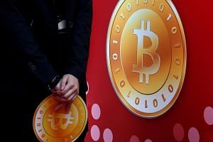 An attendant holds a bitcoin sign during the opening of Hong Kong's first bitcoin retail store.