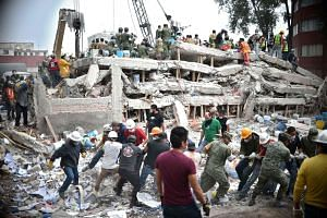 Rescuers, firefighters, policemen, soldiers and volunteers search for survivors in a flattened building in Mexico City, Sept 20, 2017.