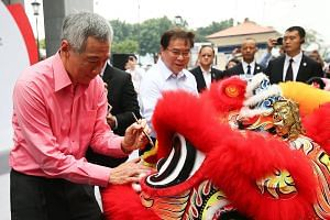 Prime Minister Lee Hsien Loong joining OCBC group chief executive Samuel Tsien (in white) in dotting the lions' eyes at a ceremony to unveil the reconstructed OCBC building in Xiamen.