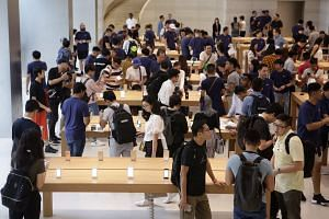 Customers trying out the functions of the new iPhone 8 and 8 Plus as they went on sale at Apple Store on Sept 22, 2017.