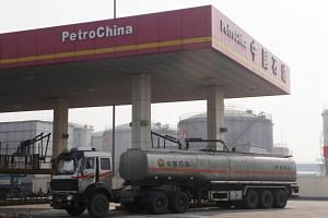 A petrol truck delivers fuel to a service station in Shenyang, northeast China, on Nov 10, 2009.