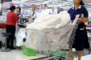 A customer leaving an NTUC FairPrice supermarket, with a trolley full of groceries that are packed in plastic bags.