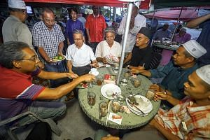 International Trade and Industry Minister Mustapa Mohamed (seated, second from left), of the ruling Umno, mingling with villagers as part of his visit to Kampung Kelaboran in Tumpat, Kelantan, yesterday. Although the opposition PAS currently controls