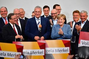 German Chancellor and Christian Democrats party (CDU) leader Angela Merkel (third from right) and top candidate for the CSU Joachim Herrmann (centre) celebrate during the election night event at the CDU party's headquarters in Berlin on Sept 24, 2017