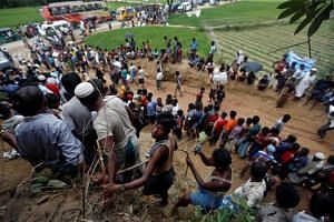 Rohingya refugees queue for aid in Cox's Bazar, Bangladesh, on Sept 24, 2017.