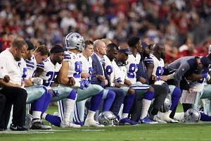 Members of the Dallas Cowboys link arms before the US national anthem at the start of the NFL game against the Arizona Cardinals.