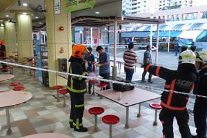 SCDF officers at the hawker centre where the object landed.