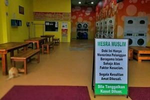 """A sign at the entrance of the laundry saying it only accepts clothes from Muslim customers for """"reasons of cleanliness""""."""