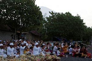 Balinese praying for safety yesterday on a beach in Amed as Mount Agung threatens to erupt. Volcanic activity near Mount Agung remains high, with hundreds of tremors recorded, officials said.