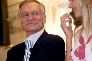 Hefner, founder of the US Playboy magazine, smiles to a bunny girl during his 75th birthday tour through Europe in Milan, Italy, on May 10, 2001.