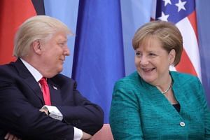 German Chancellor Angela Merkel and US President Donald Trump attend a panel discussion during the G20 summit in Hamburg, on July 8, 2017.