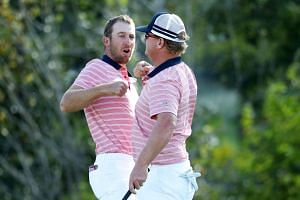 Kevin Chappell and Charlie Hoffman of the US Team celebrate on the 13th green.