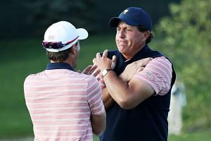 Phil Mickelson (right) and Kevin Kisner celebrate after going one up against Marc Leishman and Jason Day of Australia and the International Team.