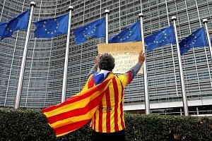 Catalan Raimon Castellvi draped in the Estelada, the separatist flag, demonstrating yesterday outside the European Commission in Brussels after Sunday's independence referendum in Catalonia. President Carles Puigdemont has appealed to the European Un