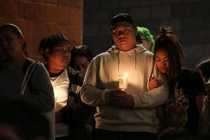 Mourners stand in silence during a candlelight vigil at the University of Nevada Las Vegas (UNLV) for victims of a mass shooting in Las Vegas on Oct 2, 2017.