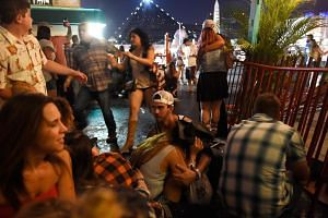 People run for cover at the Route 91 Harvest country music festival after apparent gun fire was heard.