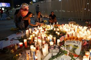 Mourners pay tributes at a makeshift memorial on the Las Vegas Strip for the victims of a mass shooting in Las Vegas.