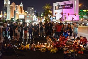 People gather and light candles at a makeshift memorial are seen near the Mandalay Hotel on the Las Vegas Strip, in Las Vegas, on Oct 3, 2017.