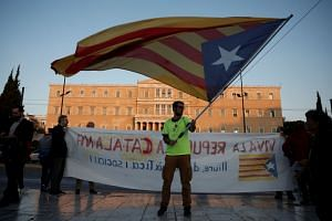 A protester waves a Catalan separatist flag in front of the parliament building, before a march to the Spanish embassy in Athens, Greece on Oct 3, 2017.