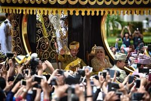 Sultan of Brunei Hassanal Bolkiah waves to the crowd during the Royal Procession.