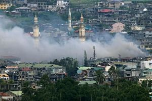 Smoke billows after a fighter jet plane dropped a bomb during an air strike in parts of Marawi city, southern Philippines on Sept 9, 2017.
