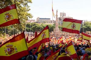 """It was a sea of Spanish flags in Colon Square in Madrid yesterday as thousands of demonstrators gathered for a """"patriotic"""" march to keep Spain united as Catalonia threatens to declare independence."""