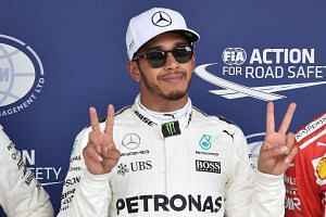 Hamilton celebrates his pole position following the qualifying session.