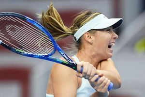 Maria Sharapova hits a return during her women's singles match against Simona Halep at the China Open tennis tournament in Beijing on Oct 4, 2017.