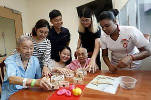 Patients Chan Wing Sum and Chong Cheng Moi try out the games created by (from second left) students Khaw June Ming, Cassandra Seah and Grace Goh. Looking on are Assistant Professor Michael Tan Koon Boon and staff nurse Nisanthi Sathasivam.