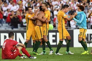 Australian players celebrates after they defeated Syria in their 2018 World Cup football qualifying match played in Sydney on Oct 10, 2017.