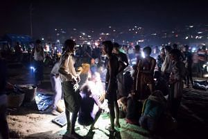 Newly-arrived Rohingya refugees, standing and sitting on the ground during the night without any shelter, wait after crossing the Naf river from Myanmar into Bangladesh, on Oct 9, 2017.
