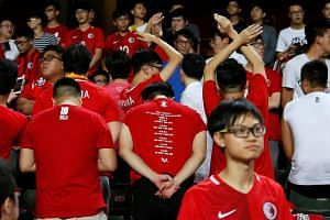 Hong Kong fans turn their backs during Chinese national anthem.