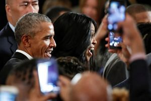 Former US President Barack Obama and former First Lady Michelle Obama talk to supporters after attending a community event in Chicago.