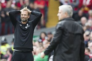 Klopp (left) and Mourinho react during the match.
