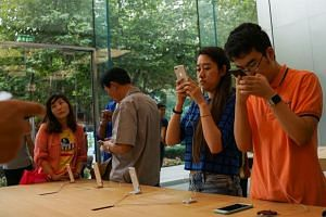 Chinese people look at Apple iPhone 8 displayed in an Apple showroom in Shanghai on Sept 22, 2017. A proliferation of consumer credit services offered by e-commerce companies now makes it easier for China's millennials to buy the latest consumer gadg