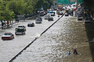 Vehicles struggling through a flooded street in Bangkok yesterday after overnight rain left many major roads submerged.