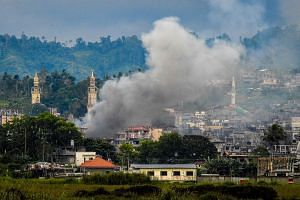 Smoke billowing from houses after aerial bombings by Philippine Airforce planes on Islamist militant positions in Marawi on the southern island of Mindanao on Sept 17, 2017. The Philippine military said on that day that it had captured the command ce