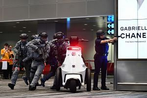 A Ground Response Force (GRF) officer (extreme right) from the Airport Police Division (APD) responding to a threat. The Rapid Deployment Troop (RDT) from the Special Operations Command (SOC), and police specialist officers also move in to respond
